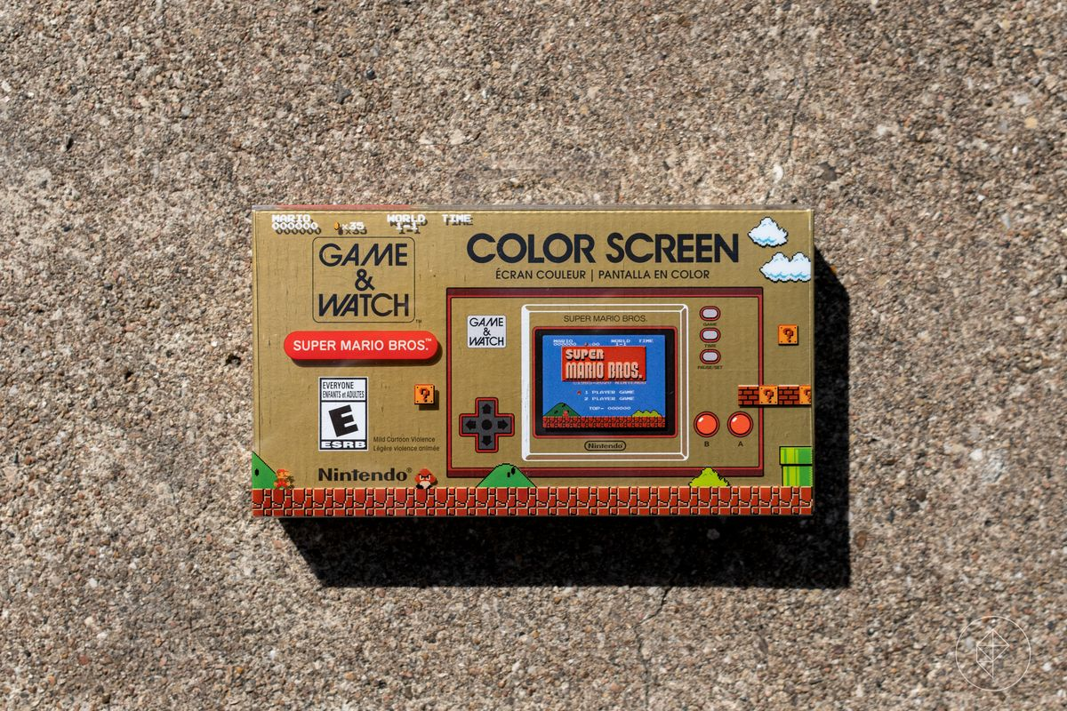 L'avant d'un jeu Nintendo en boîte & amp;  Regarder: la console Super Mario Bros. photographiée sur du béton