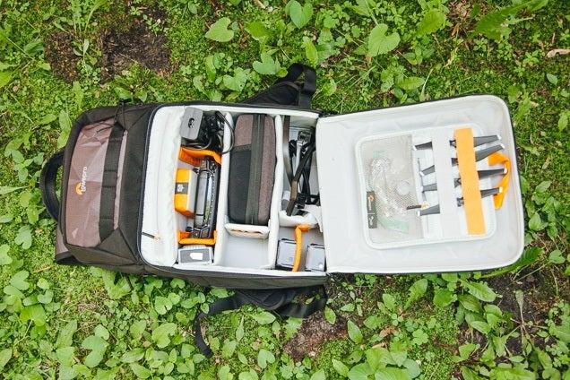Une photo aérienne de notre choix pour le meilleur sac à dos de drone au sol avec sa poche principale ouverte.  À l'intérieur, vous pouvez voir de nombreux compartiments et poches conçus pour les accessoires de drone.