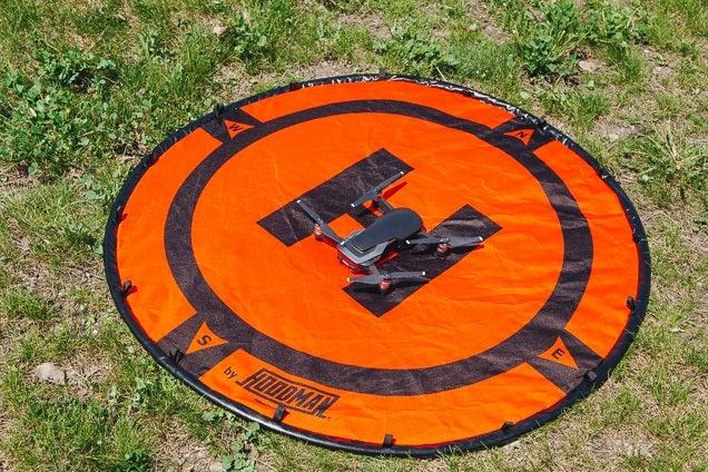Une rampe de lancement de drone ronde et orange avec des marques noires.  Un drone est assis au centre de celui-ci.