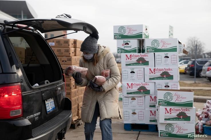 Une femme tient des marchandises alors que la banque alimentaire Forgotten Harvest distribue des marchandises avant Noël, au milieu de la maladie à coronavirus (COVID-19…