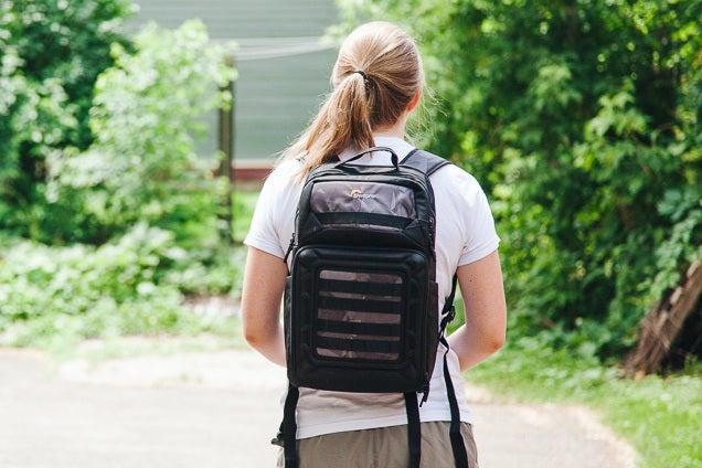 Une personne qui marche dehors avec notre choix du meilleur sac à dos de drone sur le dos.