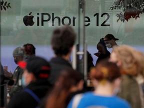 Les clients font la queue devant un Apple Store pour récupérer le nouvel iPhone 12 5G d'Apple à Brooklyn, New York, le 23 octobre 2020.
