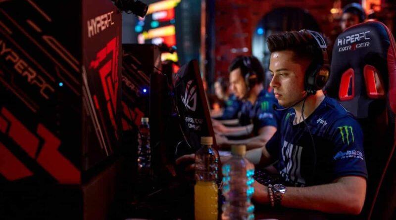 """Ancien joueur de CS: GO et actuel pro Valorant Ethan """"Ethan"""" Arnold est assis devant un PC sur une scène de tournoi avec un maillot Evil Geniuses sur"""