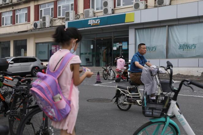 Une élève devant un point de vente du fournisseur de services éducatifs privés New Oriental, à Pékin, le 26 juillet 2021.