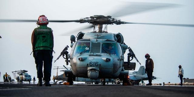 Sur cette photo fournie par l'US Navy, des marins à bord d'un hélicoptère MH-60S Seahawk sur le pont d'envol du porte-avions USS Ronald Reagan se préparent à se diriger vers un pétrolier qui a été attaqué vendredi au large des côtes d'Oman dans la mer d'Oman, 30 juillet 2021. Une attaque contre un pétrolier lié à un milliardaire israélien a tué deux membres d'équipage au large d'Oman dans la mer d'Oman, ont annoncé vendredi les autorités, marquant le premier décès après des années d'attaques ciblant les navires dans la région.  (Spécialiste de la communication de masse 2e classe Quinton A. Lee/US Navy, via AP)