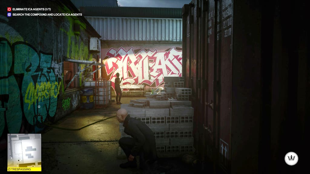 Une capture d'écran du jeu vidéo Hitman 3, montrant le tueur à gages accroupi derrière une pile de briques.