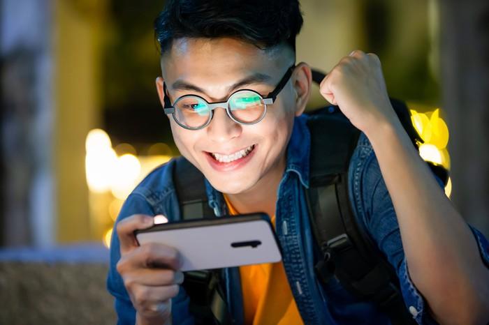 Jeune personne regardant triomphalement un smartphone.